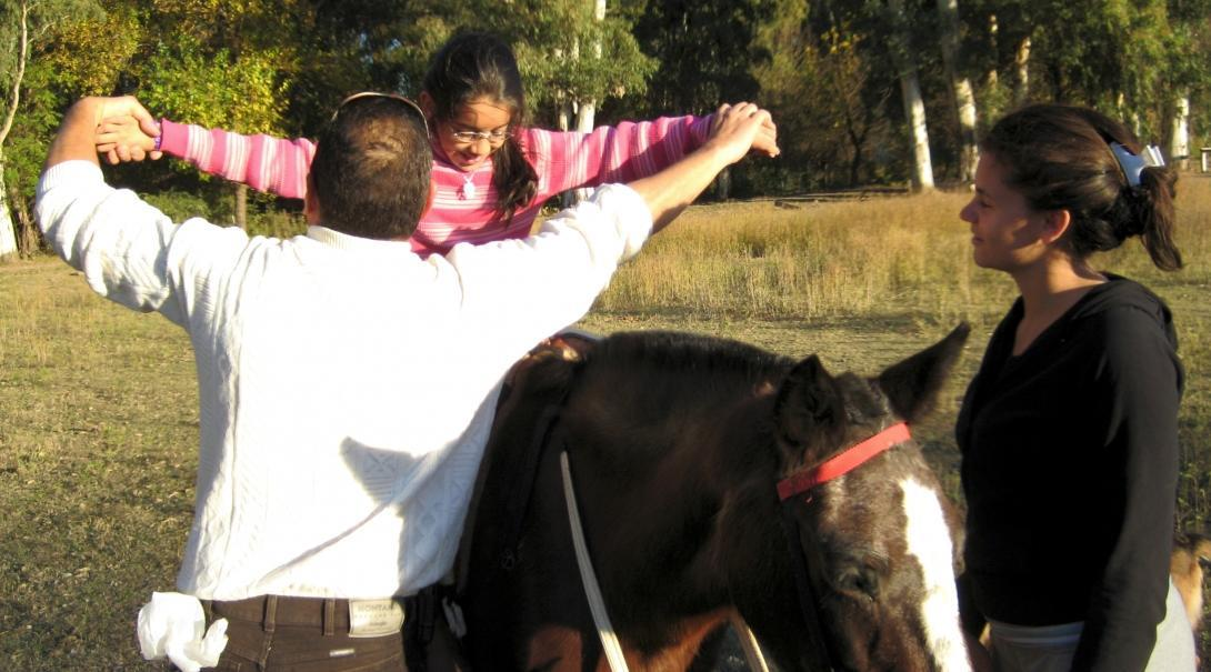 Un voluntario de Equinoterapia ayuda a una niña a montar su caballo para comenzar su sesión de terapia.